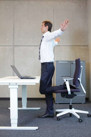 office cabinet: exercises in office. business man taking short break for stretching in standing position