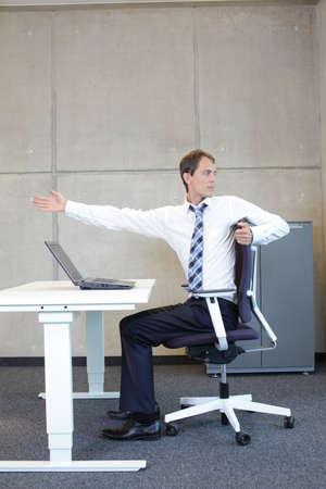 Übungen im Büro. Geschäftsmann, der Kurzurlaub zum Strecken im Sitzen am Schreibtisch Lizenzfreie Bilder