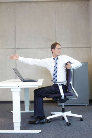 stretches: exercises in office. business man taking short break for stretching in sitting position at the desk