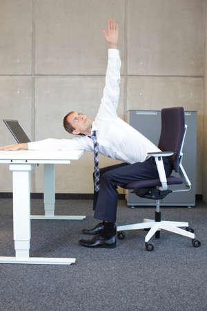 Yoga im Büro. Business-Mann, die Ausübung im Sitzen auf Sessel am Schreibtisch