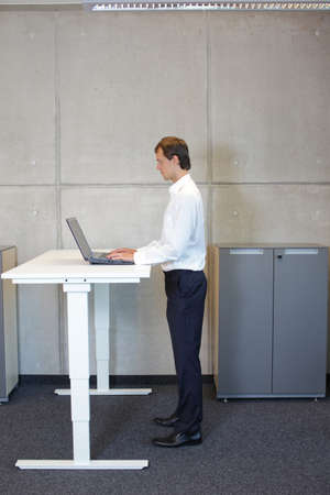 business man in white shirt standing at electrically controlled height adjustment table, working with tablet
