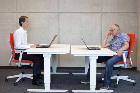 オフィスのワークステーションで悪い位置に座っている彼の同僚を見て正しい座位姿勢で働いていた男 写真素材