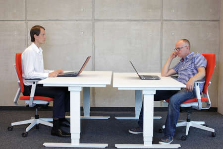 man working in correct sitting posture in office watching his colleague sitting in bad position at workstation Standard-Bild