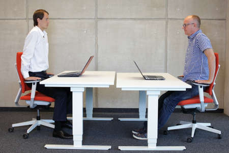 posture correction: two coworkers exercising on armchairs at  workstations in office - short break during work Stock Photo