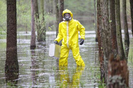 riesgo quimico: Técnico en uniforme profesional con la maleta de plata en la zona de las inundaciones contaminada