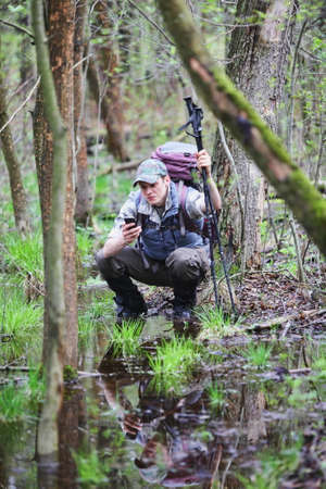 caching: Lost  crouching hiker in forest with mobile satelite navigation device checking  position Stock Photo