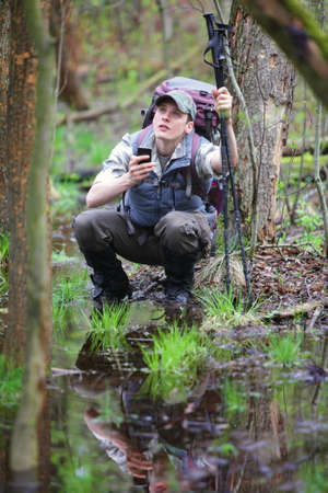 caching: Lost  crouching hiker in forest with mobile satelite navigation device checking signal