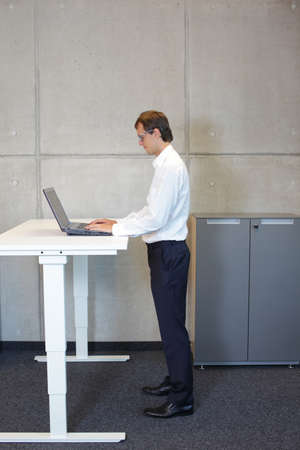 business man with eyeglasses  in white shirt standing at electrically controlled height adjustment table - full extended -  working with tablet Stockfoto