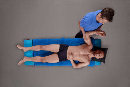 man s: Overhead view of male therapist massaging muscular man s back arm