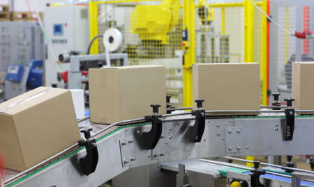 manufacture: Cardboard boxes on conveyor belt in factory