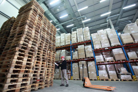 Worker with hand pallet truck at large  stack of wooden pallets reading paper in storehouse - wide angle lens photo