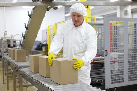 Arbeiter in weißer Uniform, Kappe und gelben Handschuhen, bei Produktionslinie, die sich mit Boxen Lizenzfreie Bilder