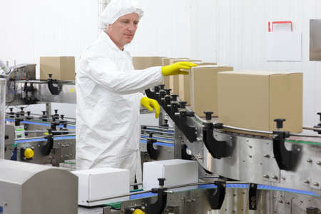 Controlling - worker in apron, cap,gloves at production line in factory