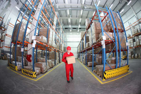 fish shop: worker in red uniform with box in the warehouse in fish-eye lens
