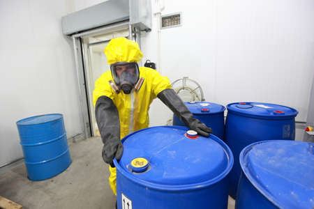 hazardous: worker in protective uniform dealing with barrels with toxic subsatnce in plant