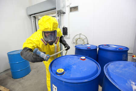 chemical hazard: Professional in uniform preparing to fill barrels with chemicals Stock Photo