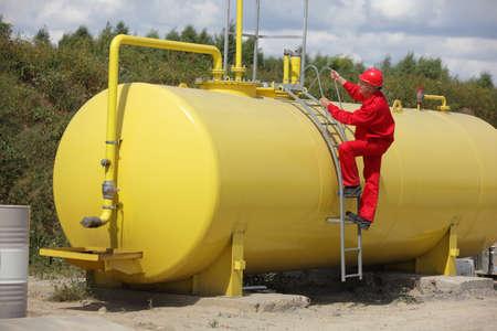 technicus in rood uniform wclimbing op grote brandstoftank