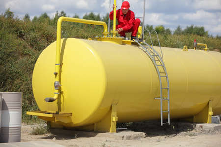 safety check: technician in red uniform working on large fuel tank