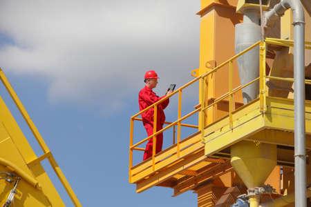 andamios: Trabajador en uniforme rojo y cheques casco datos sobre la tableta sobre la gran plataforma industrial