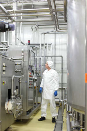 food industry specialist  in white uniform and cap controlling industrial process in plant