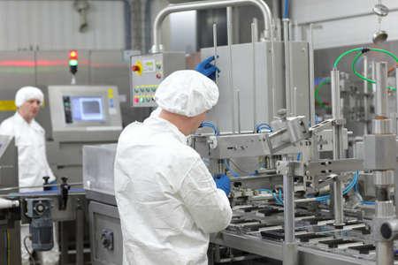 Twee arbeiders in witte schorten, mutsen en handschoenen op productielijn in de fabriek