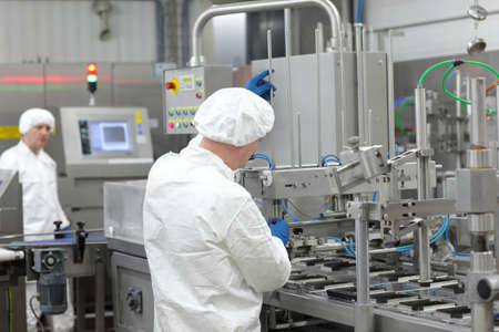 Two workers in white aprons,caps, and gloves at production line in plant