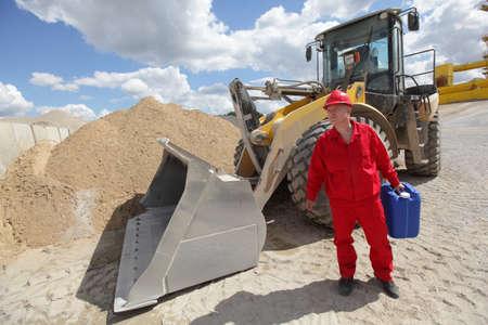 petrol can: hombre en uniforme rojo con lata de gasolina, bulldozer en el fondo - vista frontal Foto de archivo