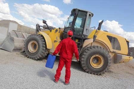 petrol can: hombre en uniforme rojo con lata de gasolina, bulldozer en el fondo, la vista atr�s