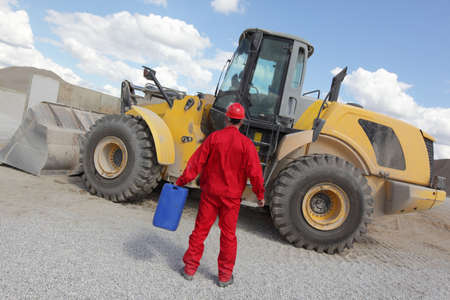 petrol can: man in red uniform with petrol can, bulldozer in background,back view