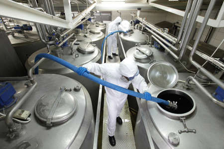 workers in protective coveralls  with blue hoses, filling large silver tanks in plant