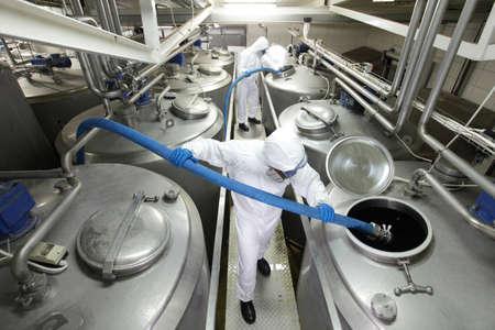 biotecnologia: trabajadores en overoles de protección con mangueras azules, llenando los tanques grandes de plata en planta