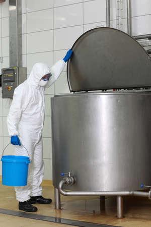 vat: technician in  white uniform with blue bucket opening industrial process tank