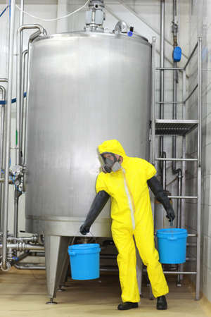 technician in yellow protective uniform with blue buckets at large industrial process tank in factory photo