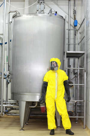 technician in yellow protective uniform with fluid in plastic container at large industrial process tank in factory photo