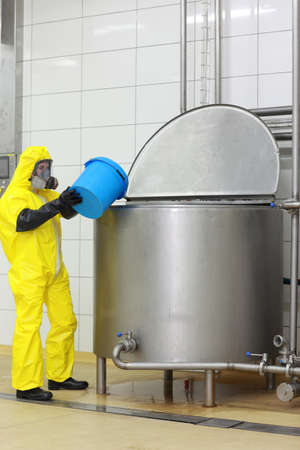 vat: technician in  yellow protective  coveralls  with blue bucket at opened industrial process tank Stock Photo