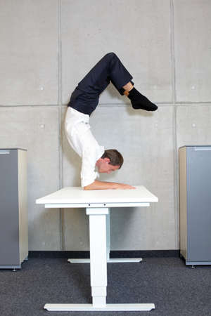 in need of space: fit,flexible business man in scorpion asana on desk in his office