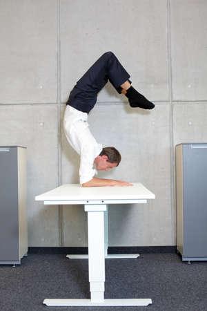 fit, flexible Business-Mann im Skorpion Asana auf Schreibtisch in seinem Büro