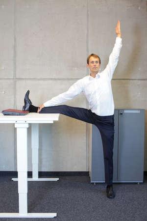 oficina de yoga - hombre de negocios que ejercita en el escritorio Foto de archivo