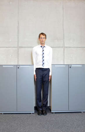 narrow: white business man standng straight between cabinets in office - concept