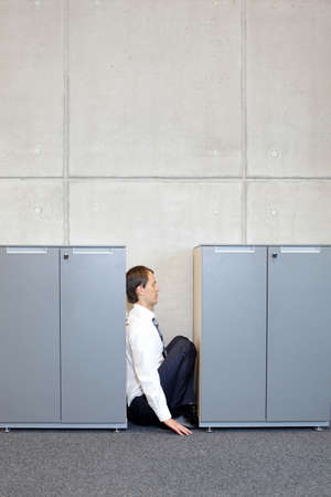 smothered: white business man crouching between cabinets in office - concept Stock Photo