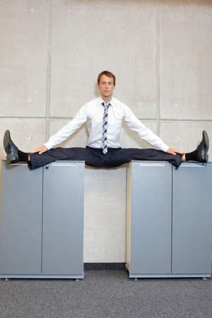 straddle: Fit, flexible business man in the center, or straddle, split position on cabinets. Stock Photo