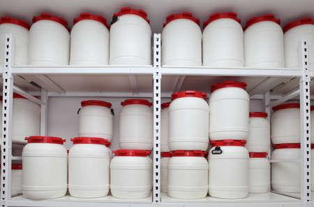 white chemical plastic barrels on shelves in storehouse Standard-Bild