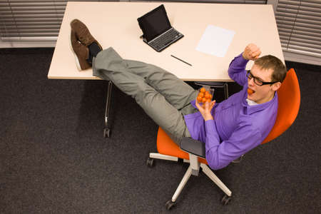 fruit eater: man sitting at with legs on the desk, heaving break in work eating cherry  tomatoes in office - healthy food concept