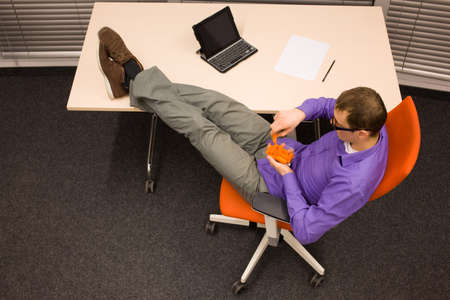 heaving: man sitting at with legs on the desk, heaving break in work eating carrot in office - healthy food concept