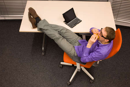 heaving: man sitting at with legs on the desk, heaving break in work eating hamburger in office Stock Photo