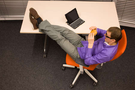 heaving: man sitting at with legs on the desk, heaving break in work  looking at hamburger and smiling in office
