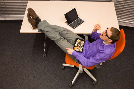 heaving: man sitting at with legs on the desk, heaving break in work eating sushi with chopsticks in office