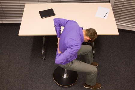 workplace wellness: man on pneumatic stool having break for exercise in office work