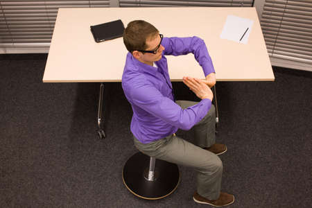 man on pneumatic stool having break for exercise in office work
