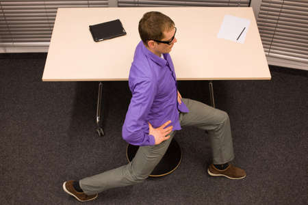 workplace wellness: office yoga - business man exercising at high desk